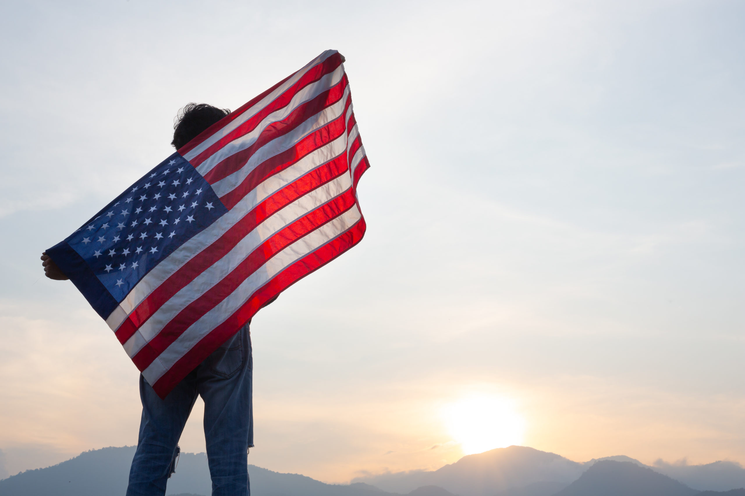 man standing and holding USA flag ิat sunrise view